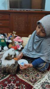 Salah satu siswi memainkan perannya merawat kucing (Foto: Reny/2021)